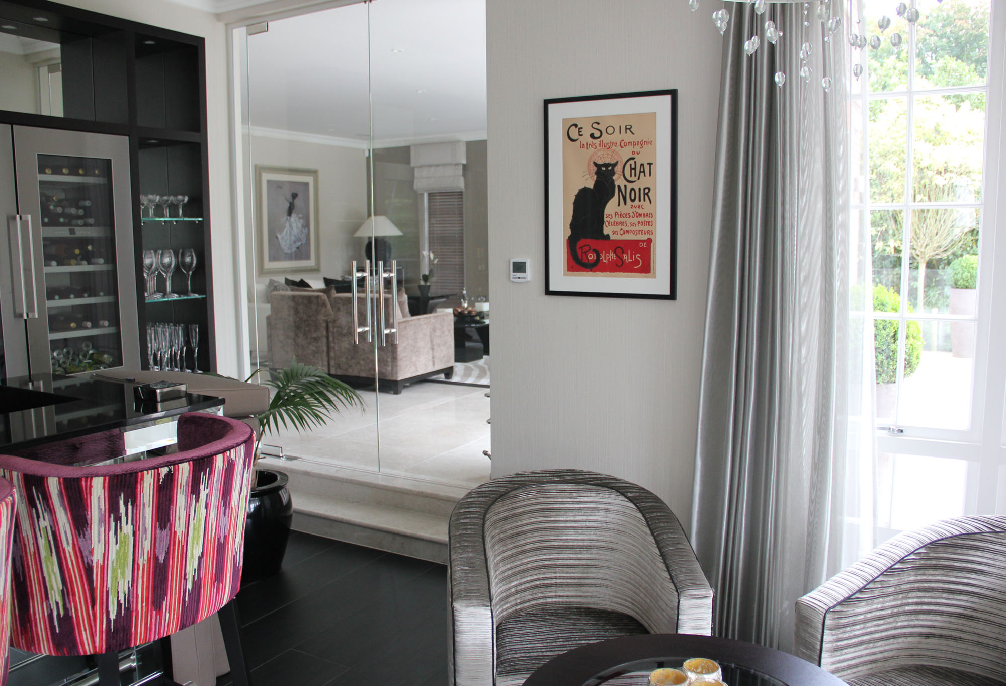 Sleek, Art Deco dining area with classic black cat poster; red, purple, black, grey