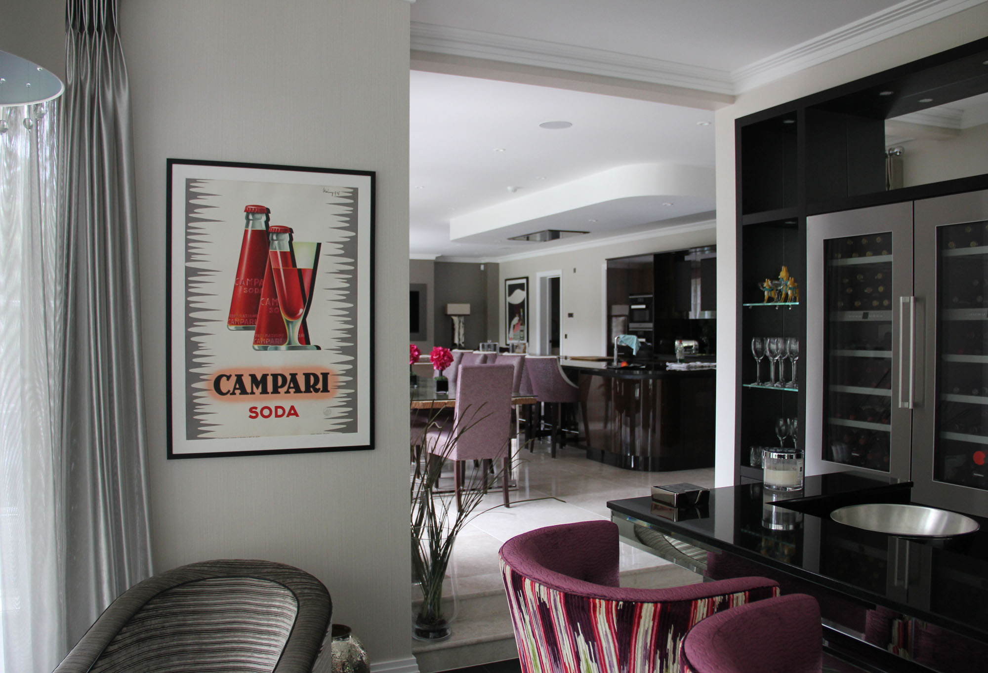 Sleek, Art Deco style living and dining area with Campari poster; red, purple, black, grey