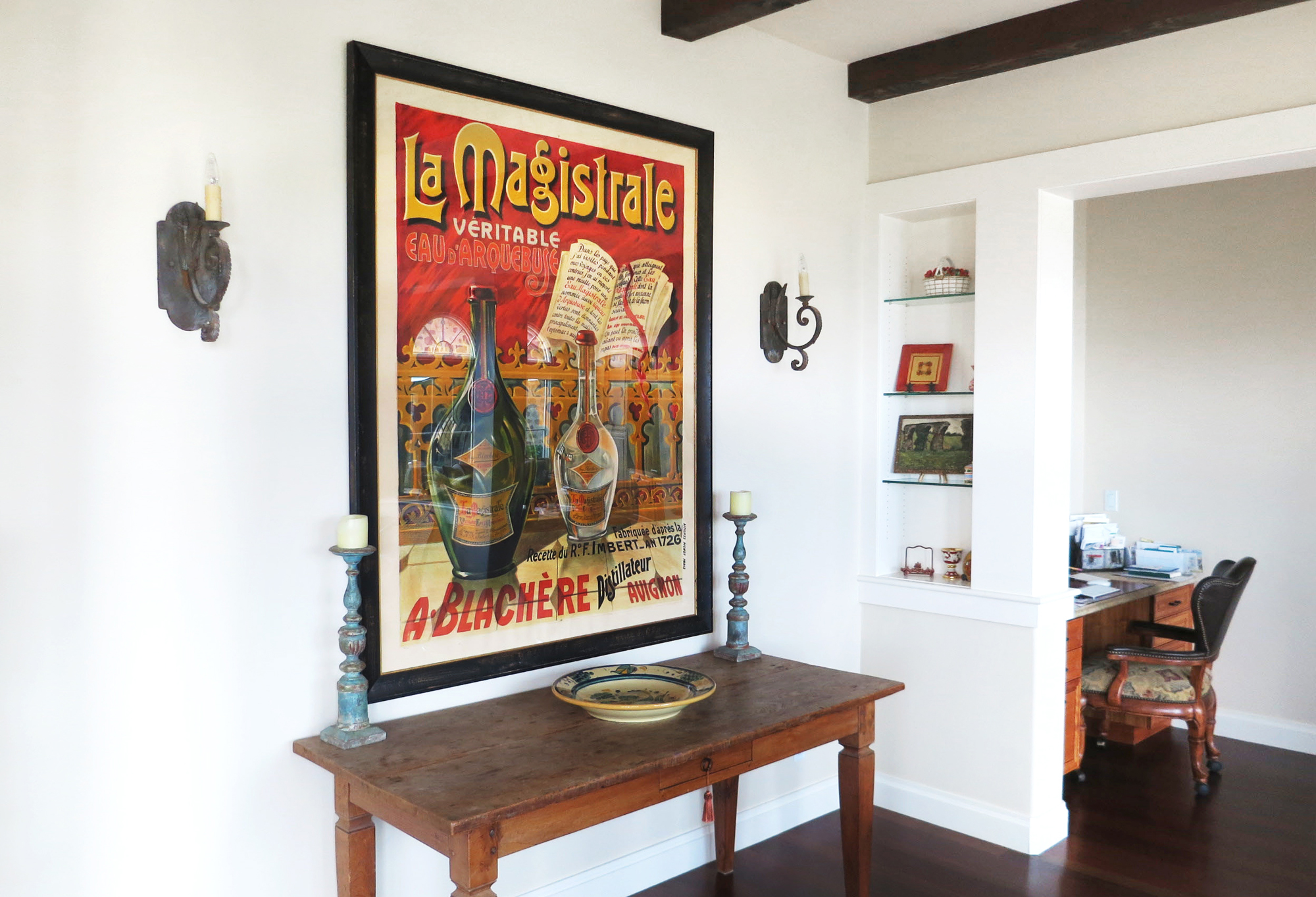 Ornate poster with bottle above farmhouse table; red, brown, white