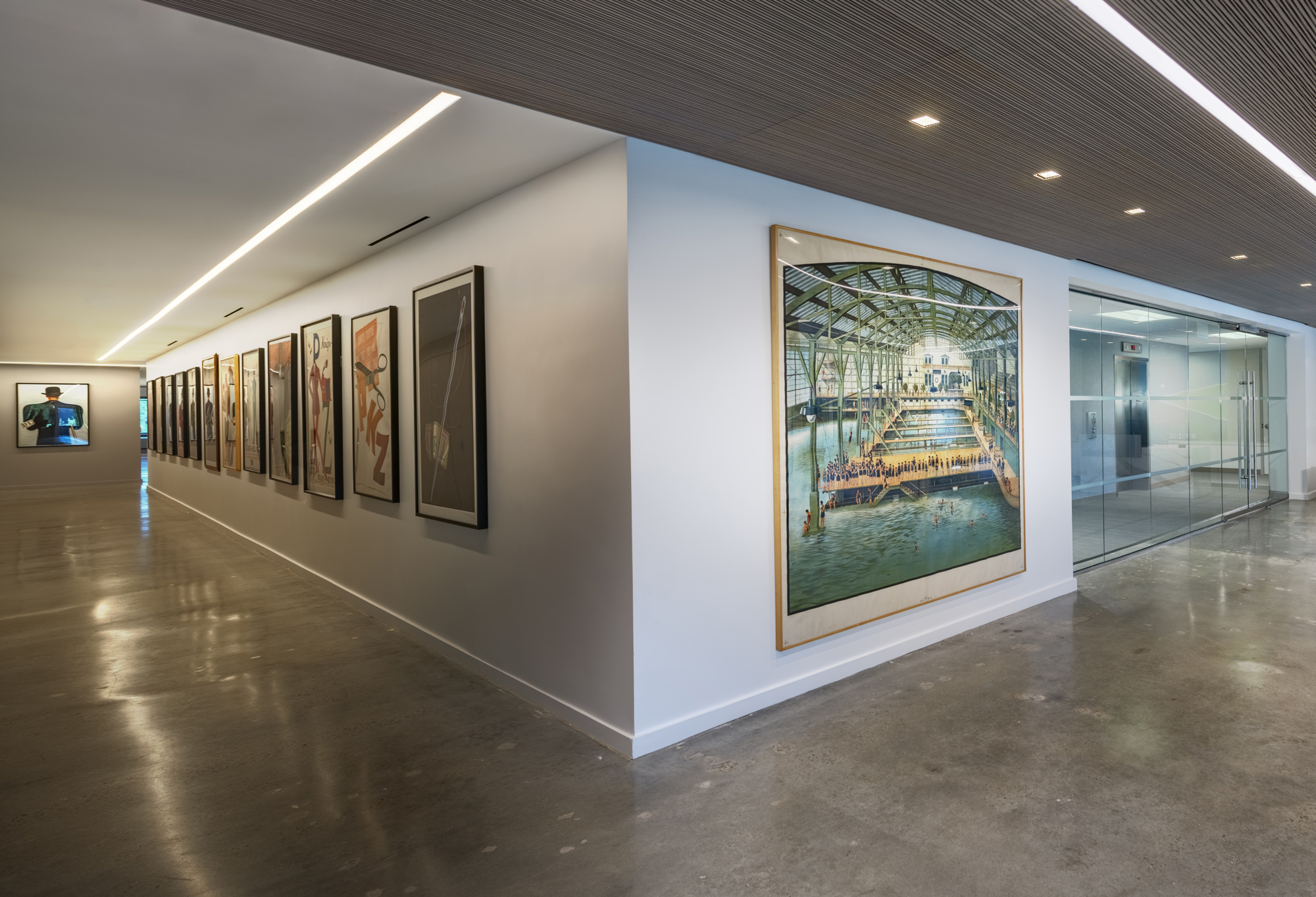Polished, modern corporate office with receding hallway of posters; white, blue, gray