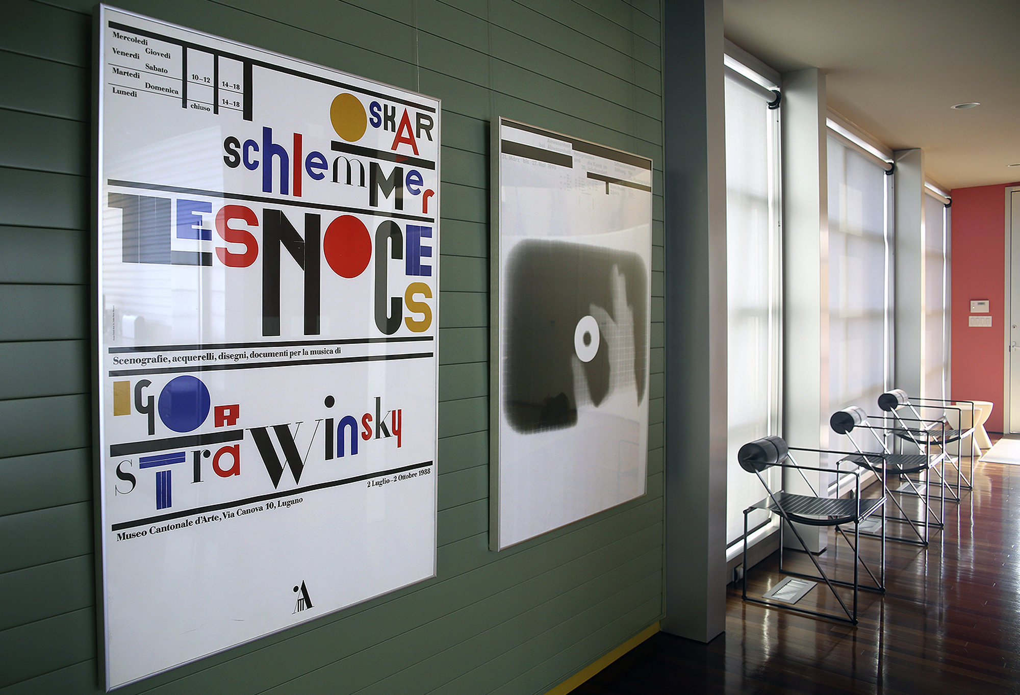 Typographic posters and modern chairs against window wall; green, red, blue, black