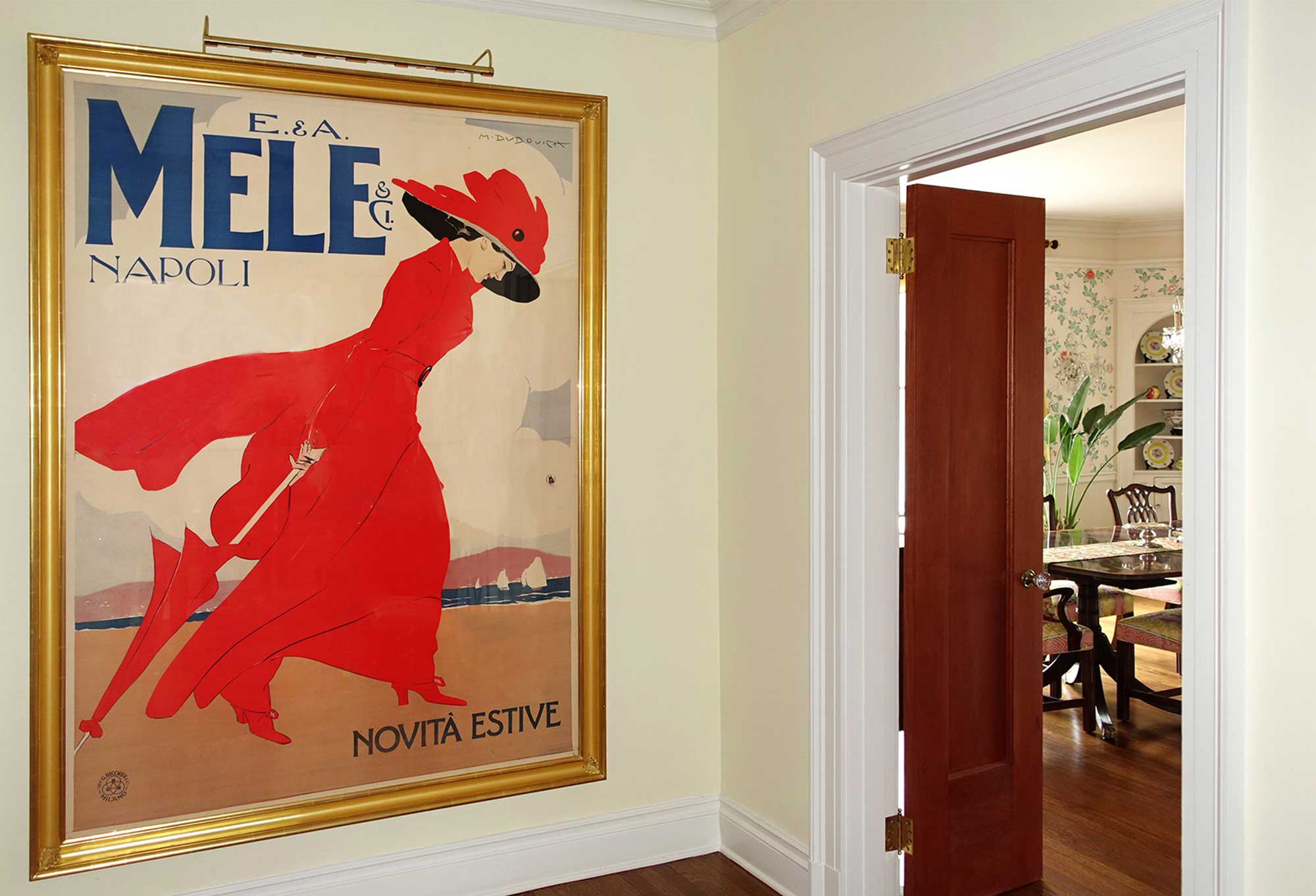 Framed fashion poster of red-clad woman at beach in hallway to dining area; red, brown, yellow