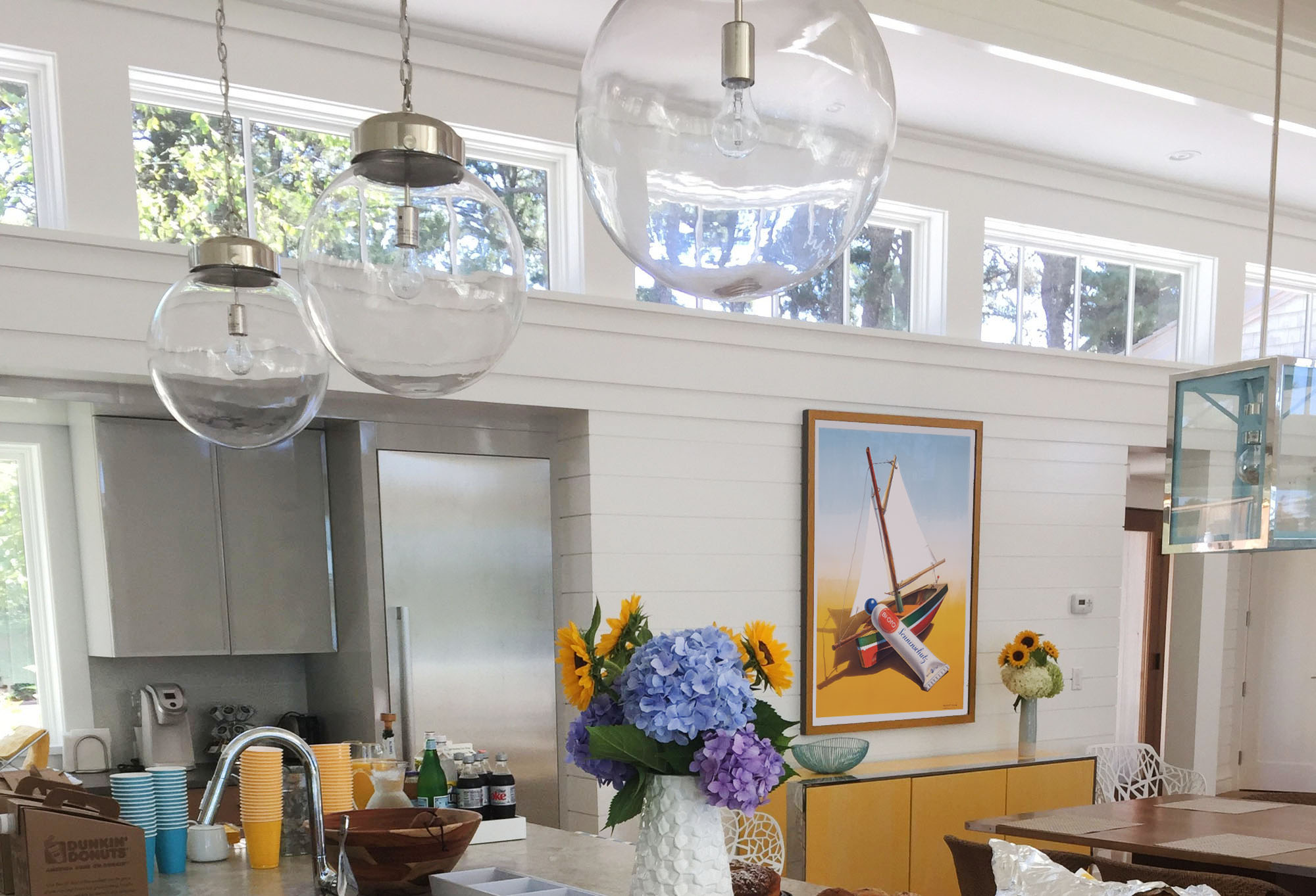 Colorful, well-lit kitchen with fresh flowers and poster with sailboat; yellow, blue, white