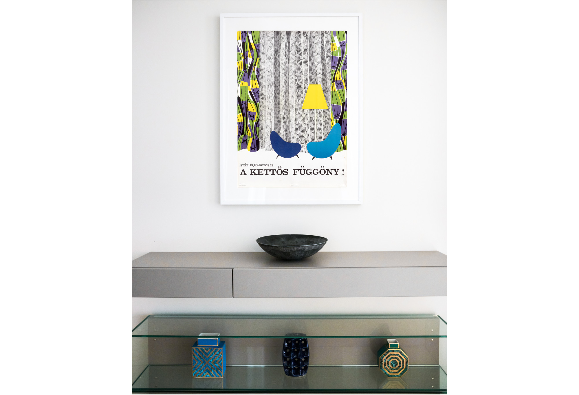 photograph of mid-century modern poster featuring chairs and curtain above decorative bowls and vases; white, grey, blue, purple, yellow, green