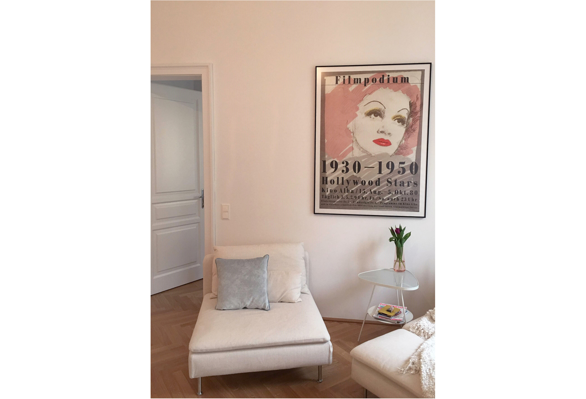framed Hollywood starlet poster above settee; pink, white, grey, brown