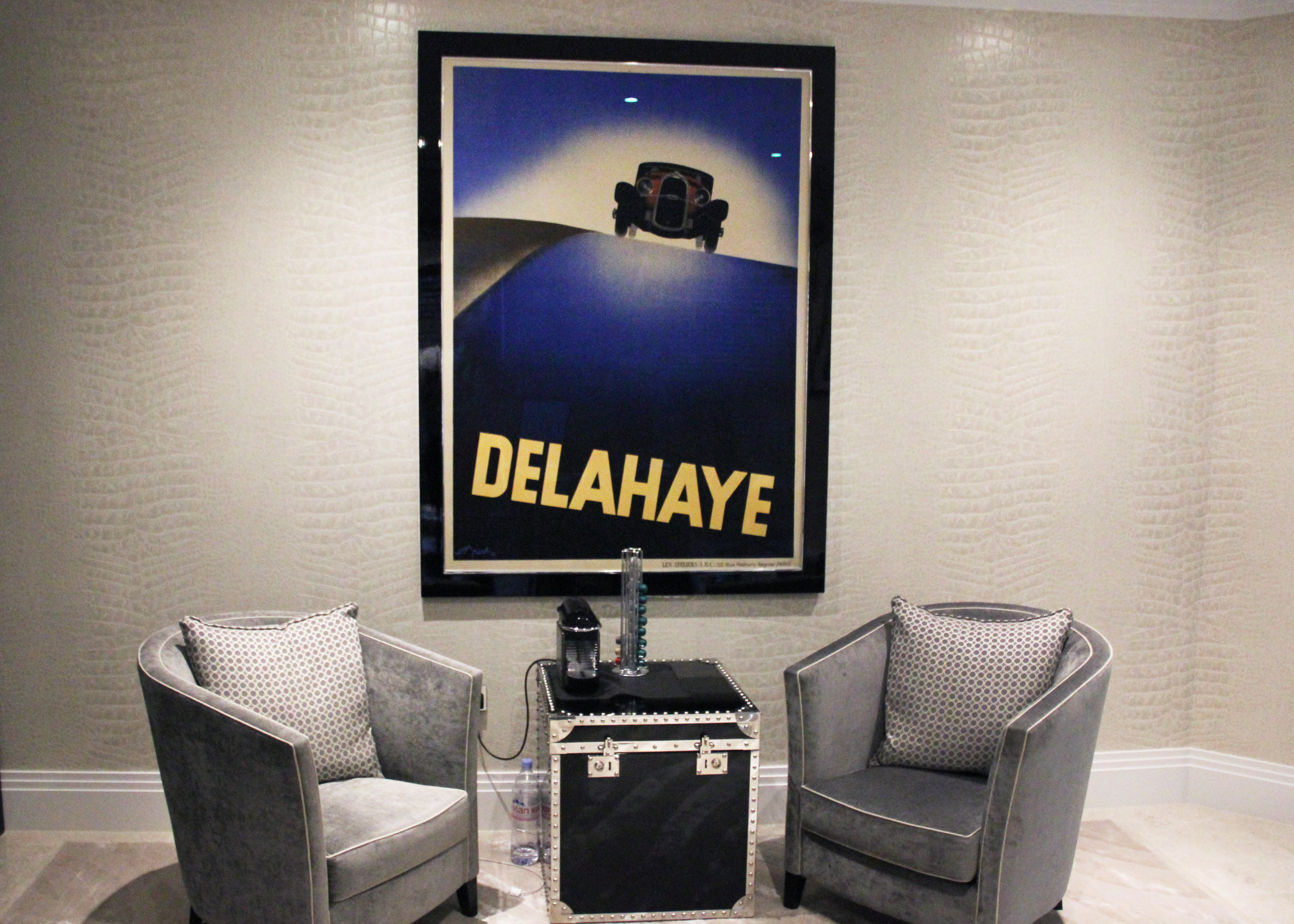 framed art deco car poster on wall behind two armchairs; blue, grey, black