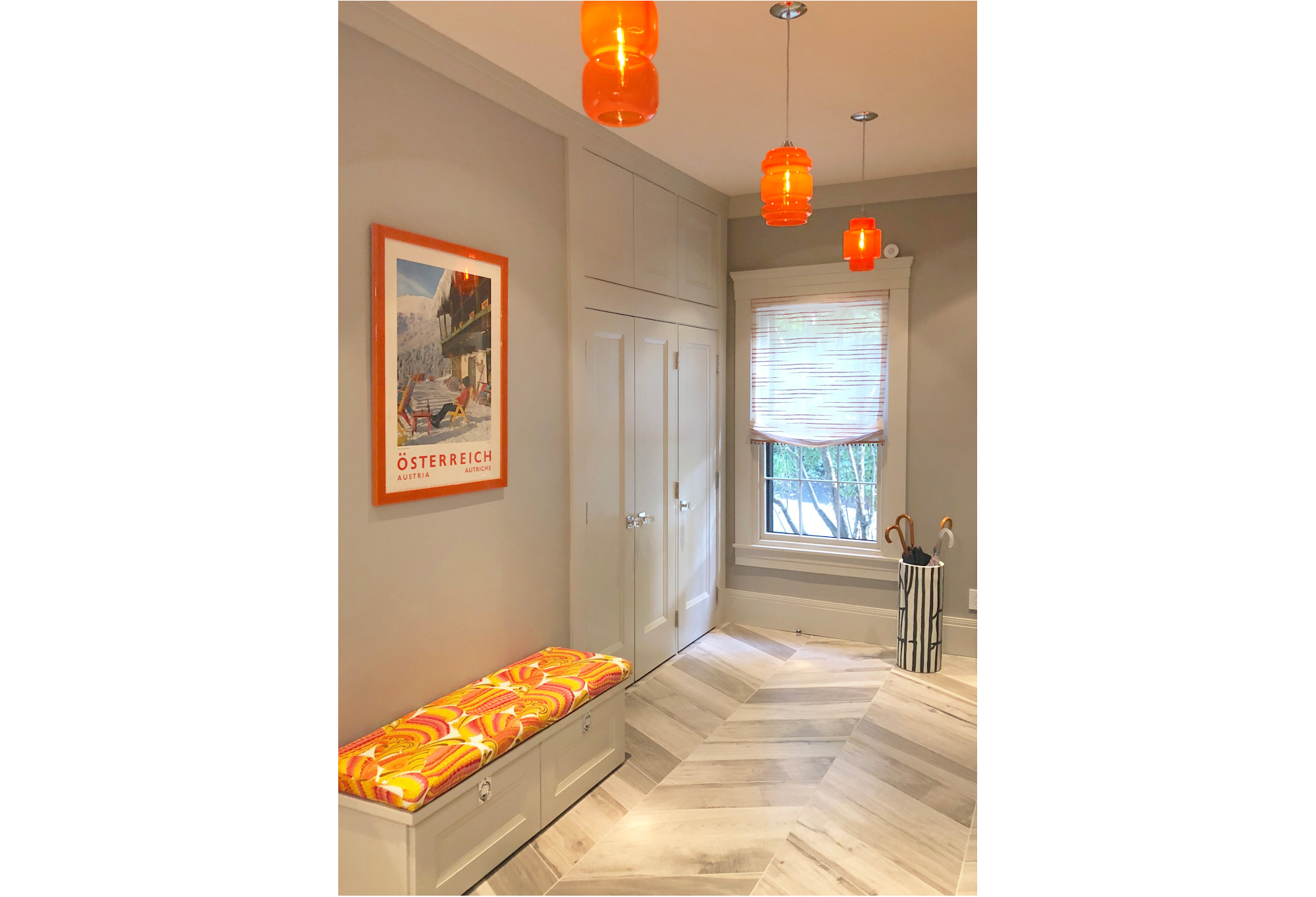 bright hallway with orange lights, bench, and framed ski poster on wall; orange, white, black