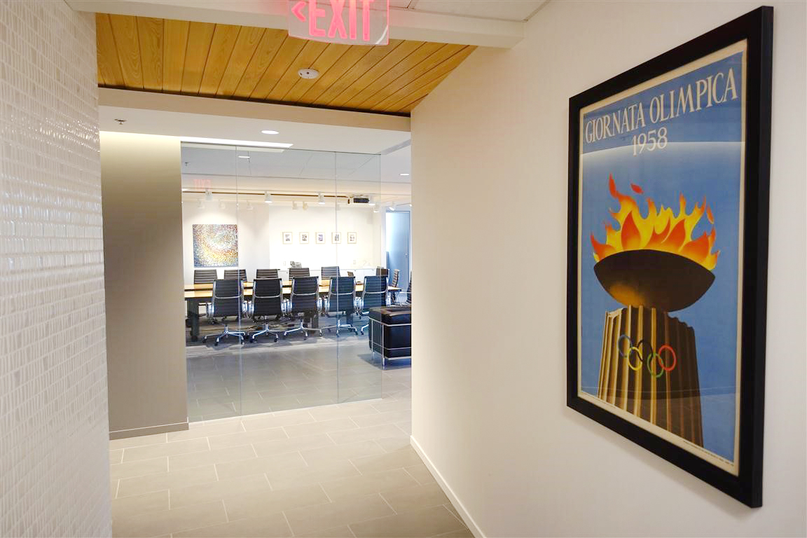 spacious office hallway with 1954 Olympic torch poster; black, white, brown, yellow, blue