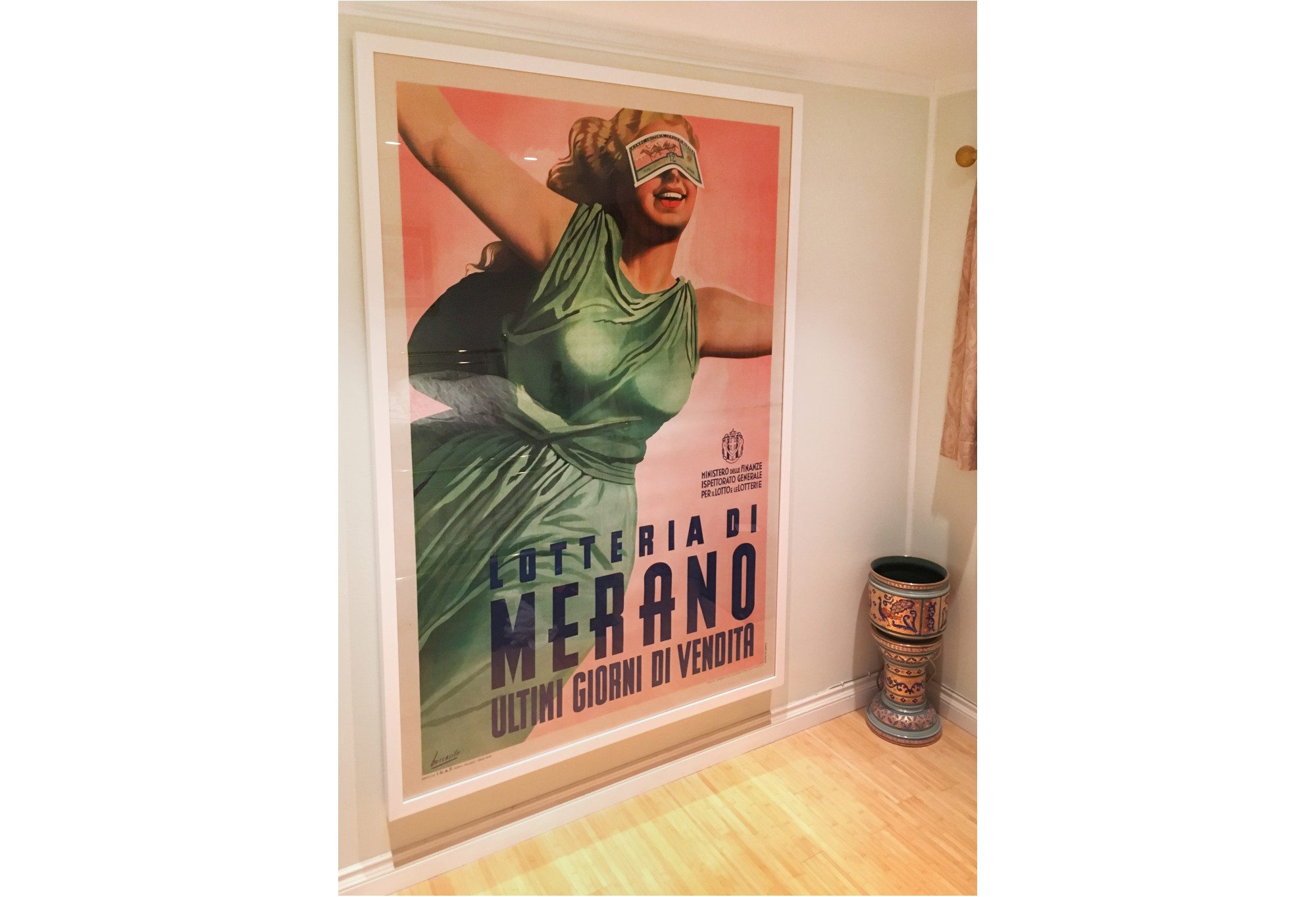large framed poster in hallway with blindfolded woman in green dress; pink, green, yellow, white