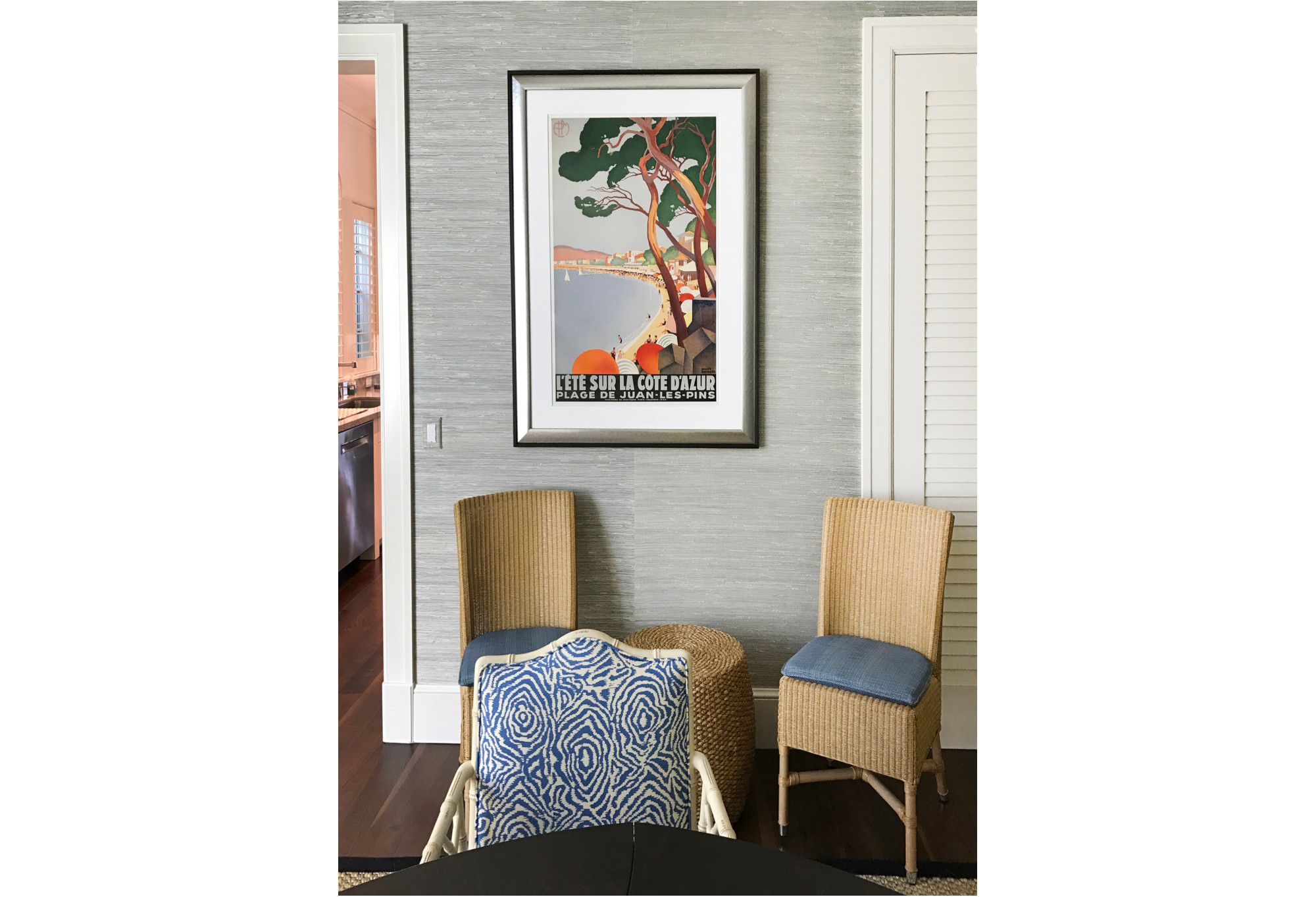 framed beach scene poster on wall with wicker chairs; blue, orange, tan, black, gray
