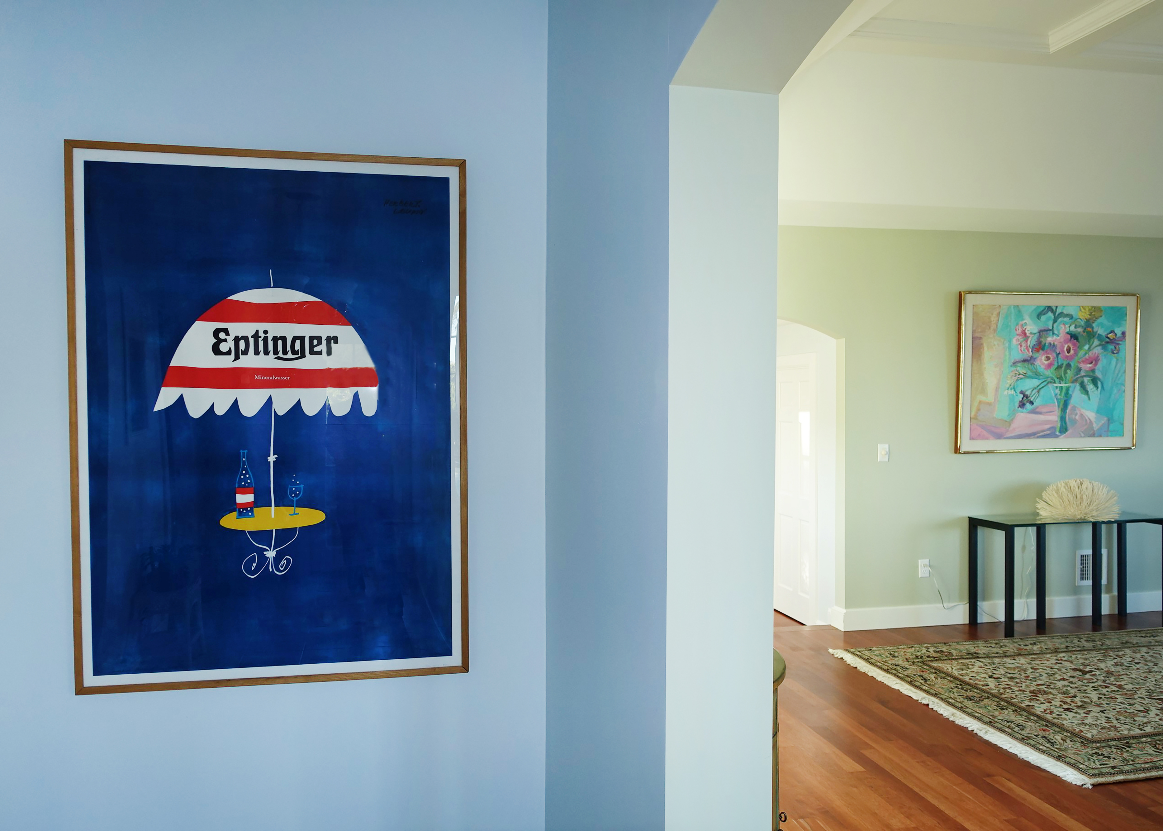 hallway with view into next room and Eptinger poster with striped umbrella; blue, red, yellow, green