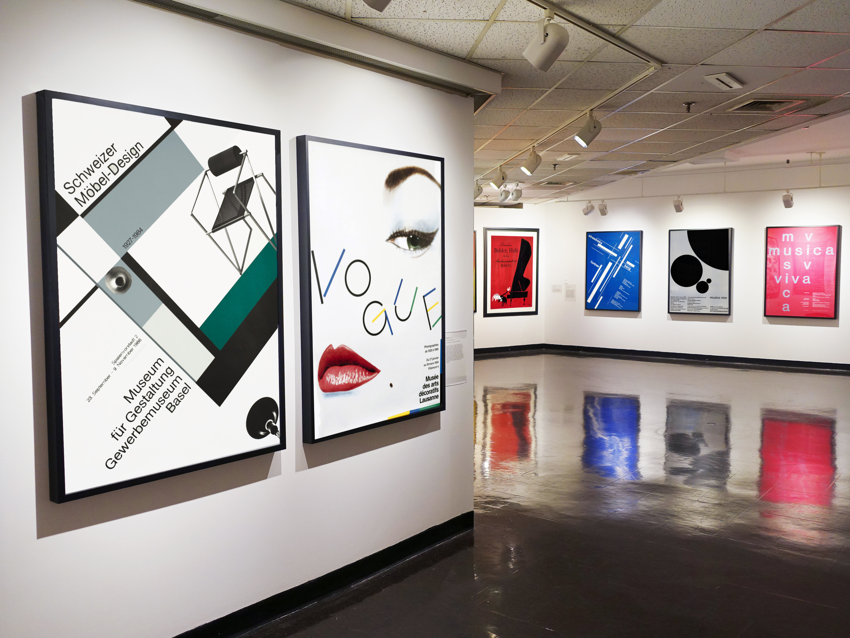 wide view of gallery with 6 posters on the walls; black, white, pink, blue, red
