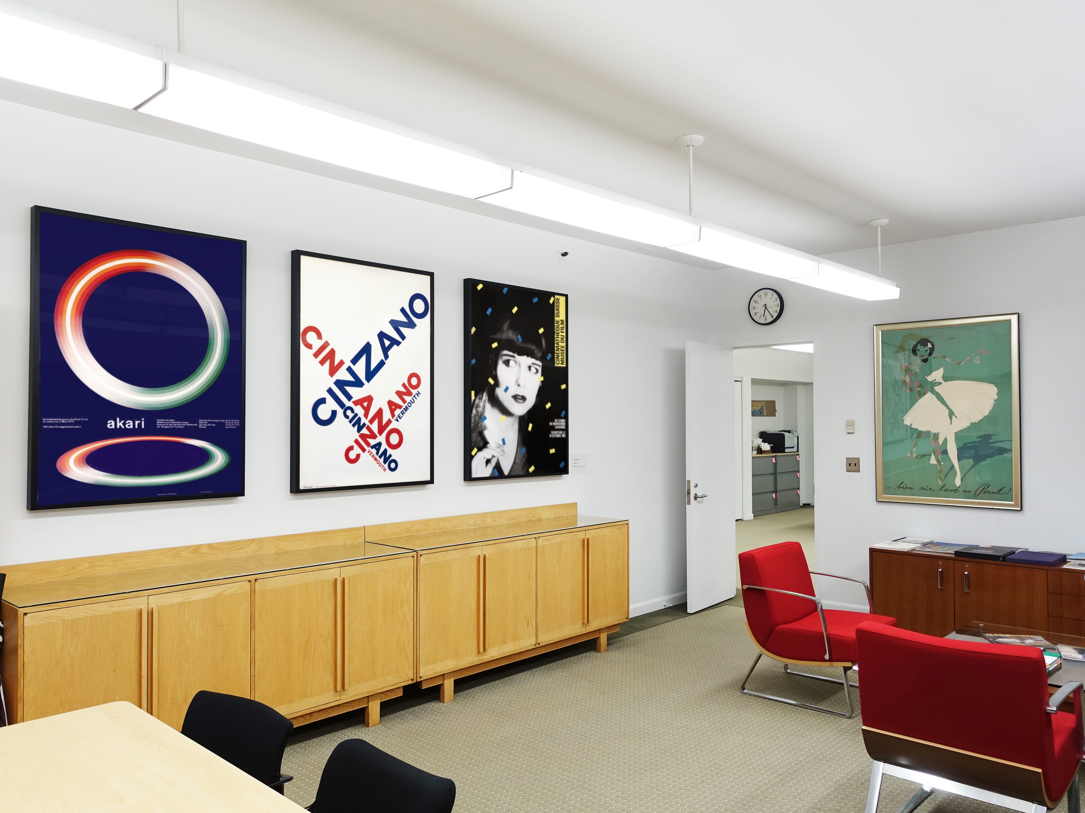 wide view of office and chairs, four posters on walls; blue, red, yellow, green