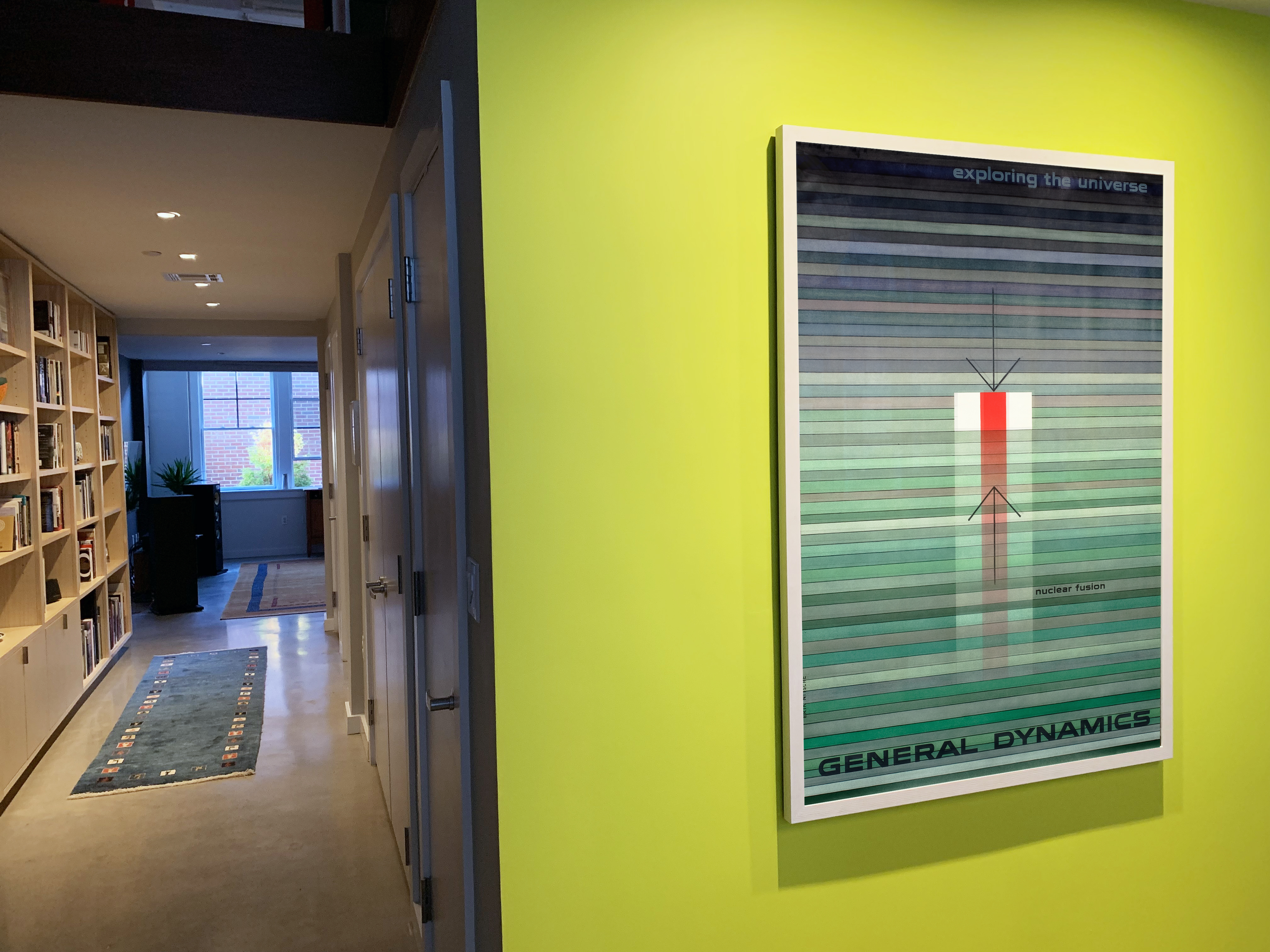 hallway with accent wall and General Dynamics poster; green, red, orange
