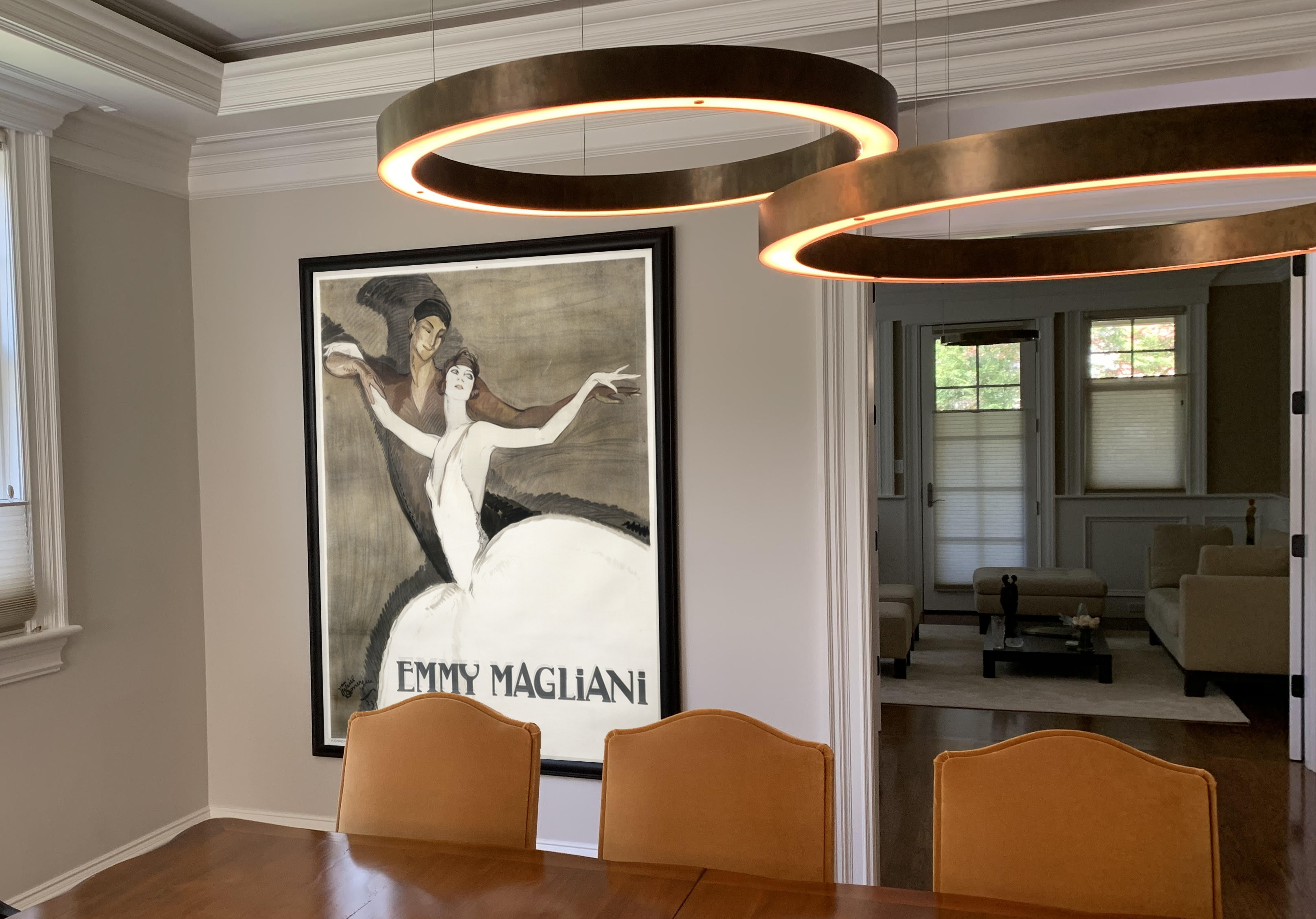 warm dining room with abstract lights and poster with man and woman ballet dancers; brown, white, orange