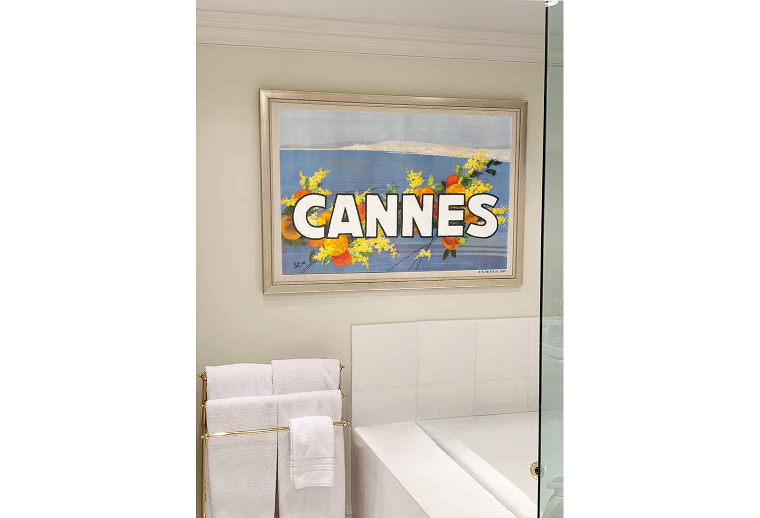 white bathroom with framed Cannes poster on wall; white, blue, orange, yellow