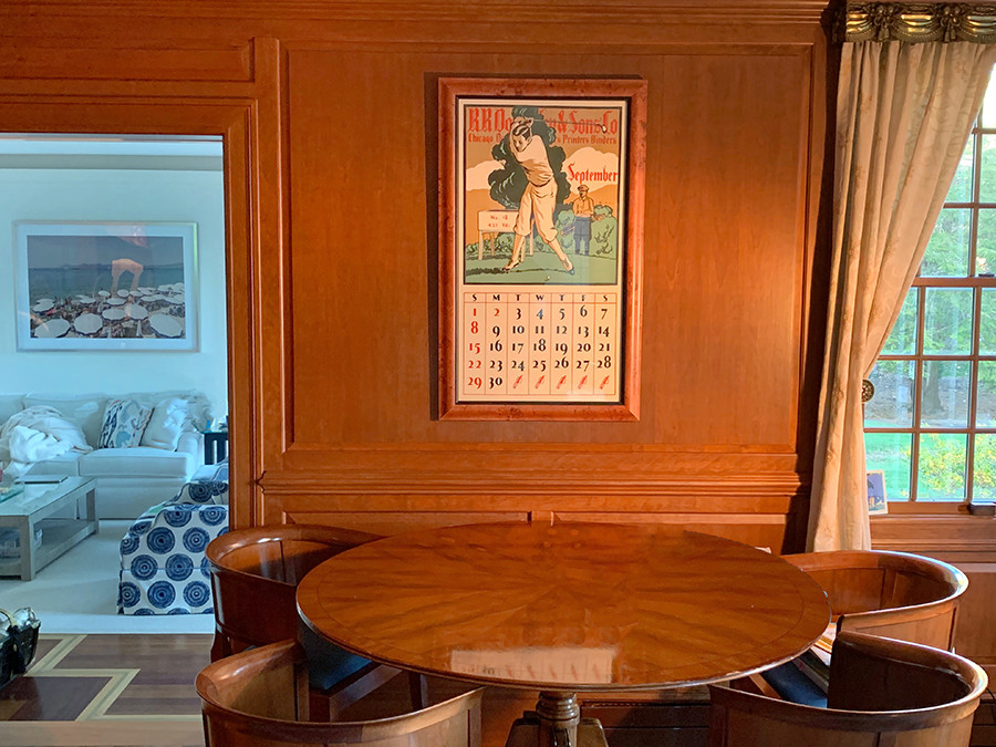 wood furnished room, framed golfer calendar, small view of side room; brown, green, white, blue